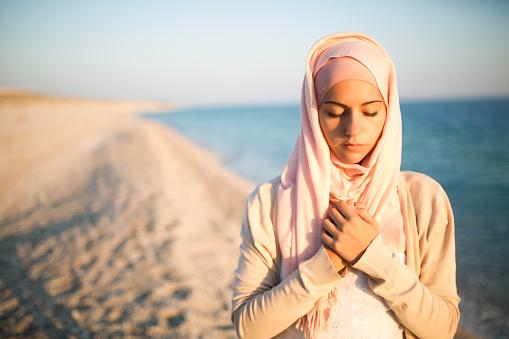 Muslim woman on the beach spiritual portrait.Humble muslim woman praying on the beach.Summer holiday,muslim woman walking on the beach