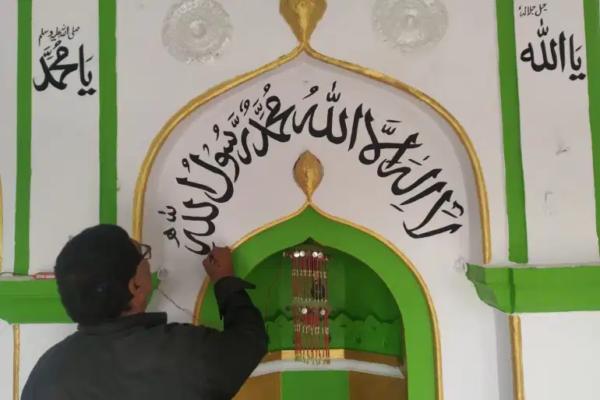 Anil Kumar Chowhan menggambar kaligrafi